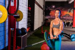 gym girl lifting a barbell with fit body - stock photo