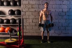 gym man holding hex dumbbells with muscles - stock photo