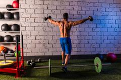 gym man rising hex dumbbells weightlifting rear - stock photo