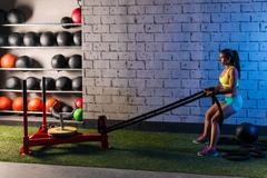 Sled rope pull woman pulling weights workout Stock Photos