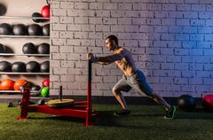 sled push man pushing weights workout - stock photo