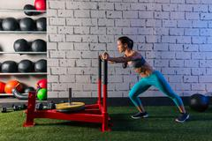 sled push woman pushing weights workout - stock photo