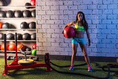 Brunette gym girl holding weighted ball Stock Photos