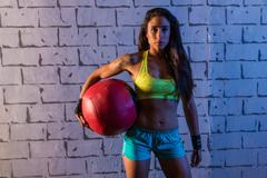 brunette gym girl holding weighted ball - stock photo