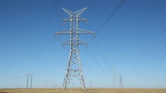 Big electrical pylons in the prairies. Traffic passes below. Alberta, Canada. Stock Footage