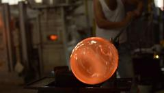 Glass virtuoso craftsman blowing hot molten glass with pipe Stock Footage