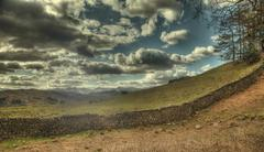 dry stone wall and clouds - stock photo