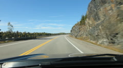 Sunny drive in Northern Ontario. Rockcut on right. Barrier on left. Stock Footage