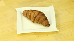 Croissant rotates on wood background Stock Footage