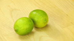 Two lime rotate on the background of wooden boards Stock Footage