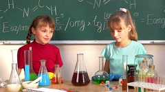 Child holding flask in chemistry class - stock footage