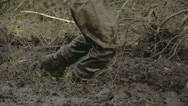 Stock Video Footage of a man in boots walking onto the thick mud fs700 4k