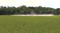 Farmer with tractor spray summer green wheat crop farm field Stock Footage