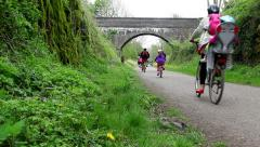 Family group cycling along the Monsal Trail Derbyshire Stock Footage