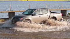 Car passing through water near dam Stock Footage