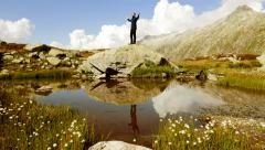 Young caucasian male hiker standing on top of stone rock raising arms Stock Footage