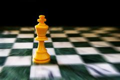 King on a chess board, against black background Stock Photos
