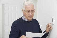 Worried senior man with bill turning down central heating thermo Stock Photos