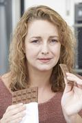 Guilty woman on diet eating chocolate bar at home Stock Photos