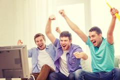 Stock Photo of happy male friends with vuvuzela watching sports