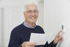 Smiling senior man with bill adjusting central heating thermosta Stock Photos