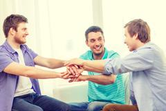 Smiling male friends with hands together at home Stock Photos