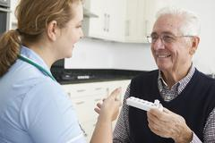 Nurse helping senior man with medication Kuvituskuvat