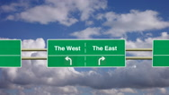 Stock Video Footage of Divided two lane road sign. To The West or The East.