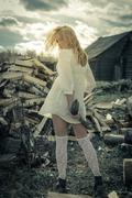 The girl with the axe on the firewood background - stock photo