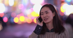 Young Asian Woman in city at night talking on cellphone 4k - stock footage