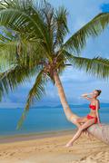 Attractive woman sunbathing on a palm tree Stock Photos