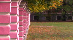 Autumn. Leaves are falling at the fence of the old park. Stock Footage