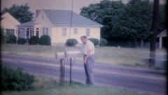 1244 - man is checking his mail box by busy road - vintage film home movie Stock Footage