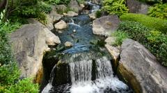 Waterfall runs into a Coy Pond at Sensoji Temple Tokyo Japan Stock Footage