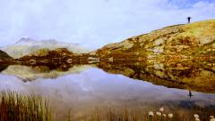 lake water reflection of hiker standing on top of mountain cliff - stock footage