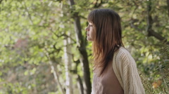 A woman stands in the park and smiles when she sees the camera - stock footage