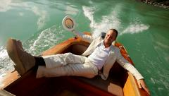 young handsome man relaxing on boat deck wearing white casual suit - stock footage