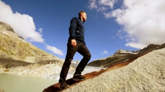 Recreational activity of young male hiker walking in mountain landscape scenery Stock Footage