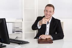 happy young businessman sitting in his office give advice for customers. - stock photo