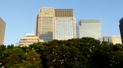 Zoom Out of Office Buildings Surrounded by Trees in Central Tokyo Japan Stock Footage