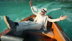 Casual dressed man enjoying easy life on boat ride. raising hand pose Stock Footage