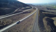 Freeway traffic in dry hills area on a sunny day with vehicles driving Stock Footage