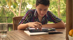 Young teenager doing homework and using tablet computer on terrace HD - stock footage