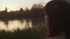 A woman stands at the edge of a pond at sunset in a park in slow motion, close - stock footage