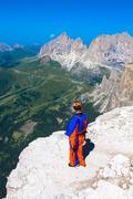 base jumper jumping off a big cliff in dolomites,italy, breathtaking - stock photo