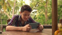 Young teenager playing game on smartphone sitting on terrace HD Stock Footage