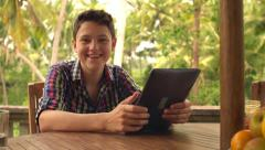 Portrait of young happy teenager with tablet computer on terrace HD Stock Footage