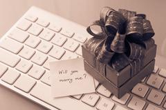 romantic gift with marry me? love message, valentine's day concept on sepia t - stock photo