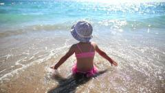 Little girl on the shore looking at the sea and playing with the waves. Stock Footage