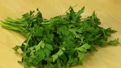 Bunch of parsley rotates on a wooden board Stock Footage